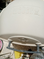 Used Weber gas grill and a round glass table in Dubai, UAE
